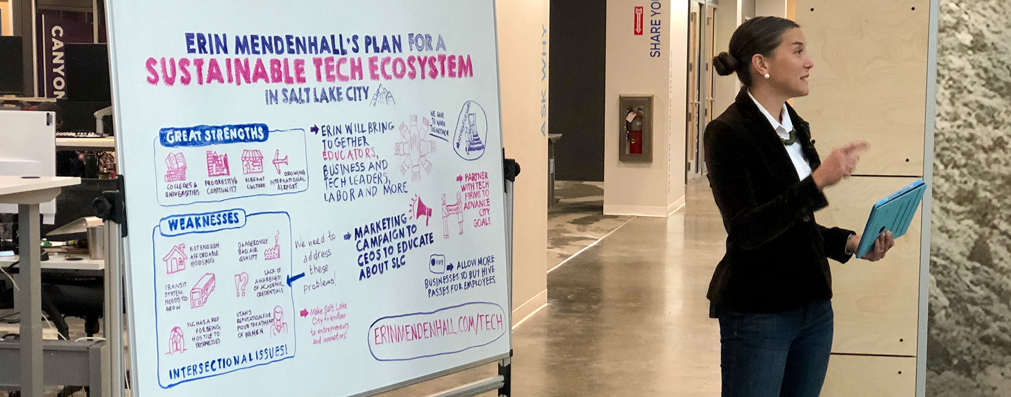 Photo of Erin Mendenhall in front of a white board with an illustration of her tech ecosystem plan